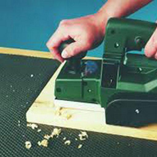 antislipmat onder houten plank die bewerkt wordt met elektrische schaaf
